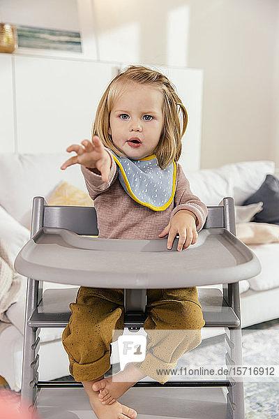Kleines Mädchen sitzt zu Hause auf einem Hochstuhl und streckt die Hand aus
