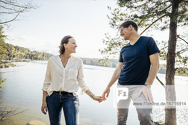 Happy couple hand in hand at the lakeside  Forstsee  Carinthia  Austria