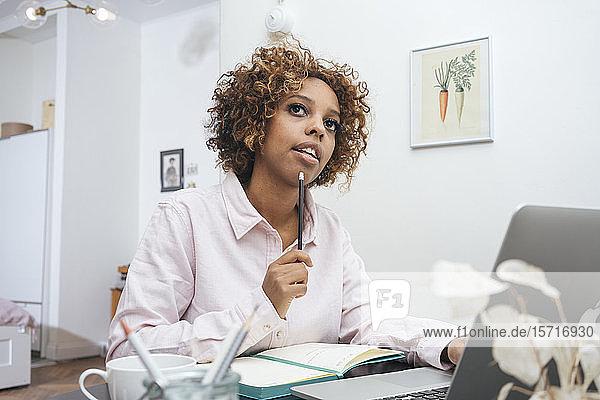 Junge Frau  die zu Hause arbeitet und Notizen macht