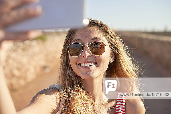 Smiling woman with sunglasses  taking selfie at sunset