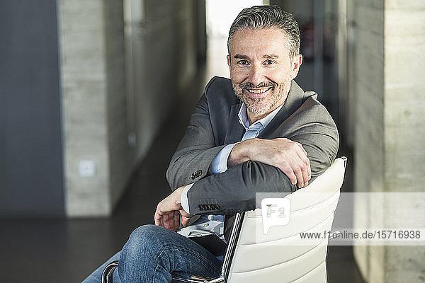 Porträt eines lächelnden reifen Geschäftsmannes  der auf einem Stuhl im Büro sitzt