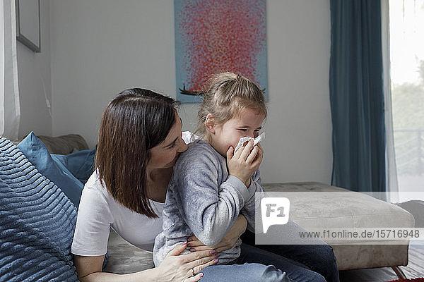 Mutter sitzt mit der Tochter auf der Couch im heimischen Wohnzimmer und schnäuzt sich die Nase