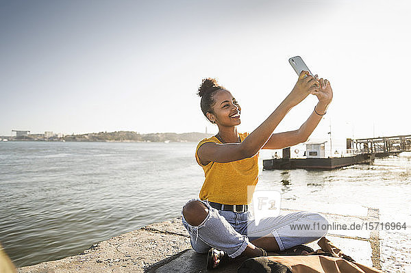 Happy young woman sitting on pier at the waterfront taking a selfie  Lisbon  Portugal