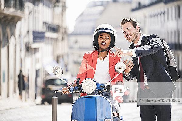 Geschäftsmann mit Handy im Gespräch mit Frau auf Motorroller in der Stadt  Lissabon  Portugal