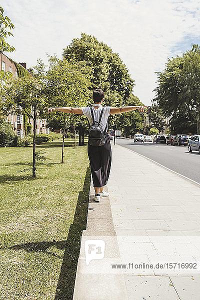 Rückenansicht einer Frau mit Rucksack  die auf einer Wand balanciert