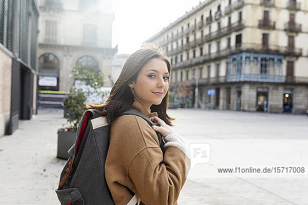Portrait of young woman with backpack in the city  Barcelona  Spain