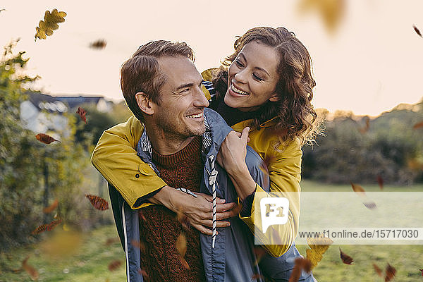 Man giving woman a piggyback ride outdoors in autumn