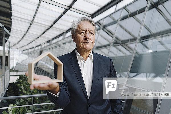Porträt eines leitenden Geschäftsmannes  der ein Hausmodell im Amt hält
