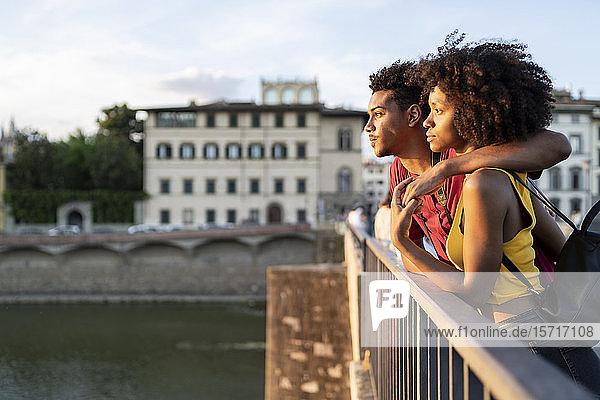 Junges Touristenpaar auf einer Brücke über den Arno bei Sonnenuntergang  Florenz  Italien