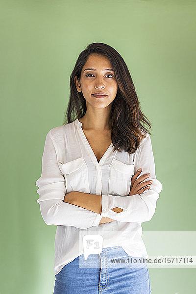 Porträt einer jungen Geschäftsfrau  die vor einer grünen Wand steht