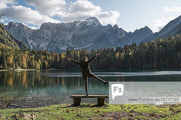 Rückansicht einer Wanderin  die auf einem Bein auf einer Bank in Laghi di Fusine  Friaul-Julisch Venetien  Italien  steht