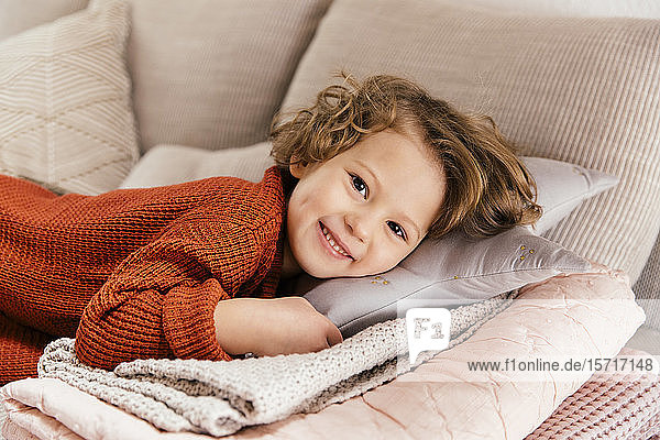 Portrait of smiling girl lying on couch at home