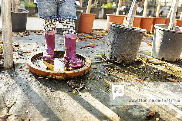 Crop view of little girl wearing Wellington Boots playing at pant nursery