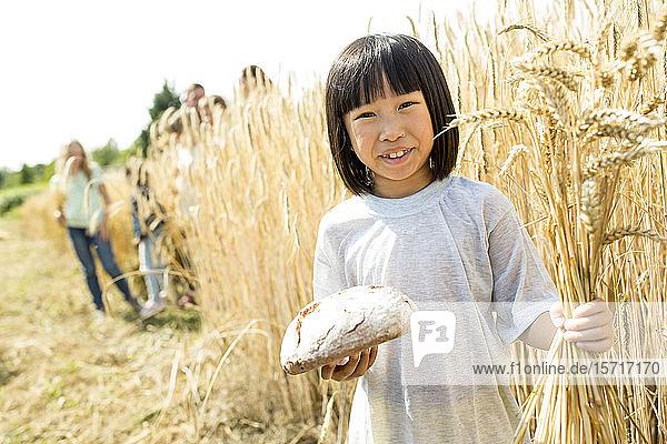Kleines asiatisches Mädchen steht auf dem Feld  hält Brot und Weizenähren