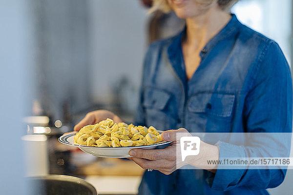 Nahaufnahme einer Frau  die zu Hause in der Küche einen Teller mit Tortellini hält Nahaufnahme einer Frau, die zu Hause in der Küche einen Teller mit Tortellini hält
