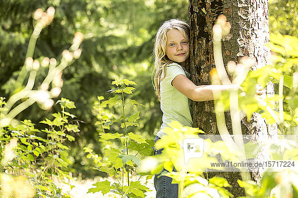 Kleines Mädchen umarmt Baum im Wald