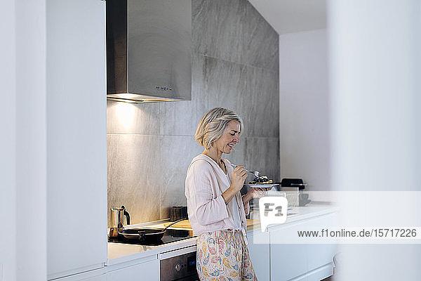 Reife Frau hält zu Hause in der Küche einen Teller mit Pfannkuchen