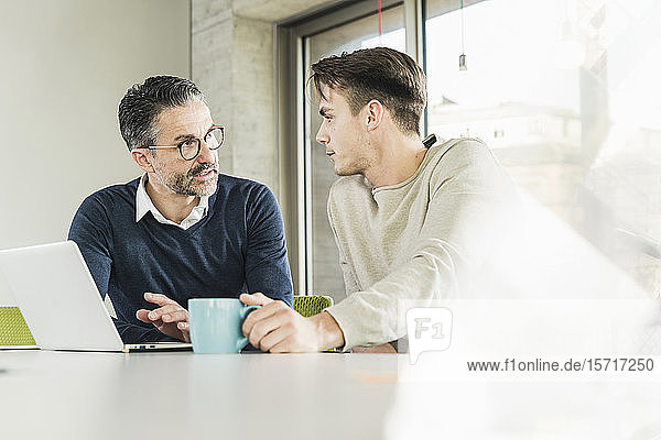 Mature businessman and young man talking at desk in office