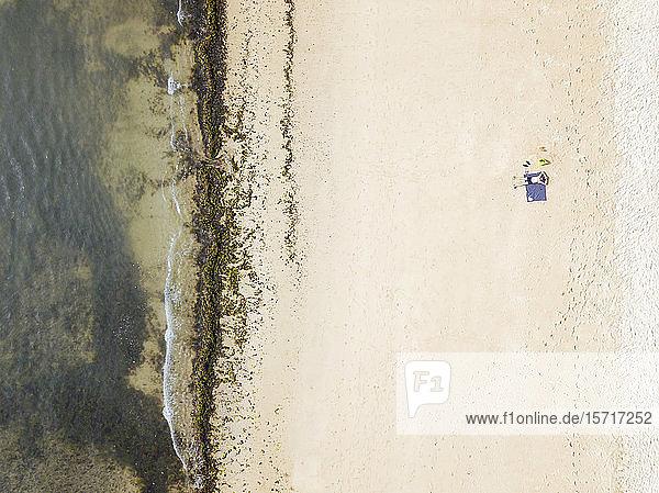 Indonesien  Bali  Luftaufnahme eines Mannes beim Sonnenbaden am sandigen Küstenstrand von Nusa Dua