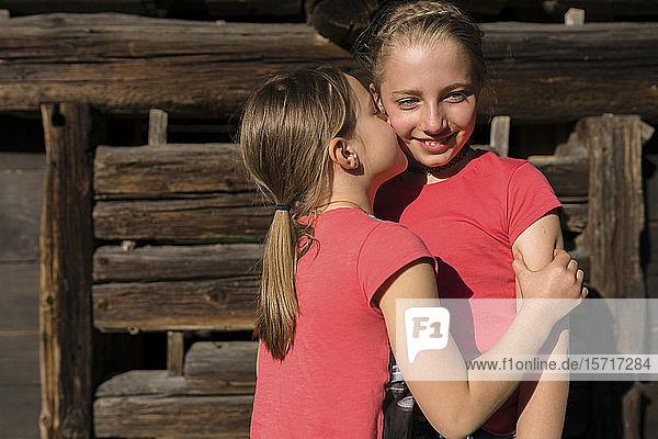 Mädchen umarmt und küsst ihre Schwester