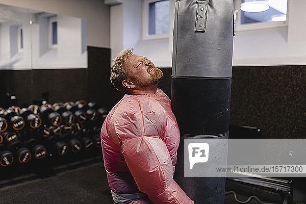 Man wearing pink bodybuilder costume practicing in gym