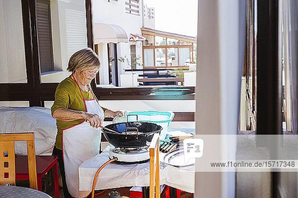 Ältere Frau bereitet spanisches Weihnachtsgebäck Pestinos