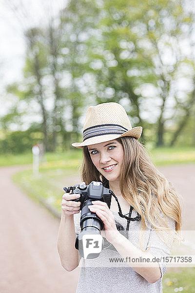 Porträt einer lächelnden jungen Frau  die zwei verschiedene Kameras im Freien vergleicht