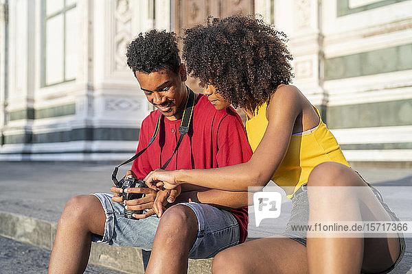 Glückliches junges Touristenpaar macht eine Pause in der Stadt und schaut in die Kamera  Florenz  Italien