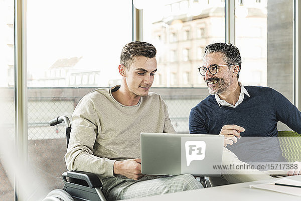 Mature businessman and young man in wheelchair using laptop in office