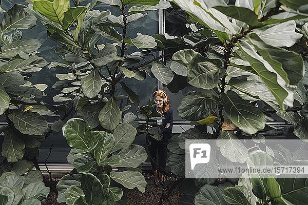 Geschäftsfrau hört Musik umgeben von großen Pflanzen