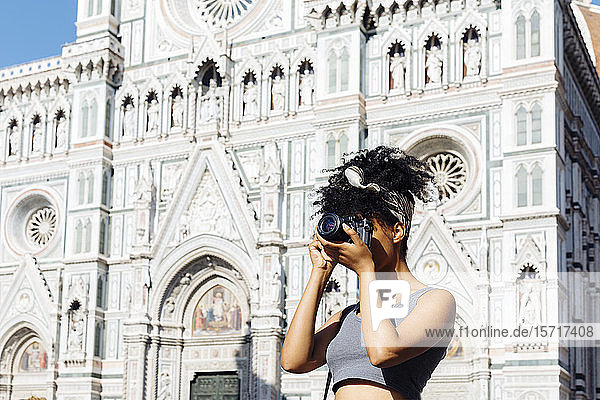 Young woman taking photo with camera in front of cathedral  Florence  Italy