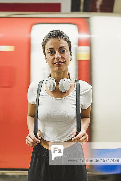 Porträt einer Frau mit Rucksack vor einem U-Bahn-Zug stehend  London  UK