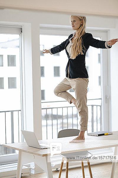 Junge Geschäftsfrau praktiziert Yoga auf dem Schreibtisch im Büro