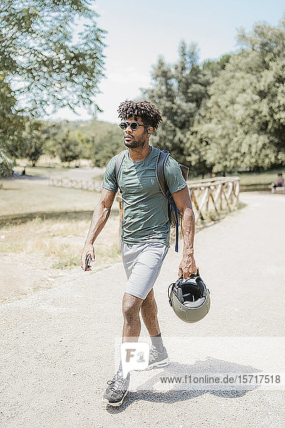 Young man with helmet walking in park