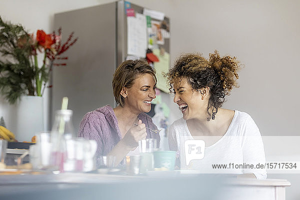 Two happy women sitting and talking at kitchen table at home