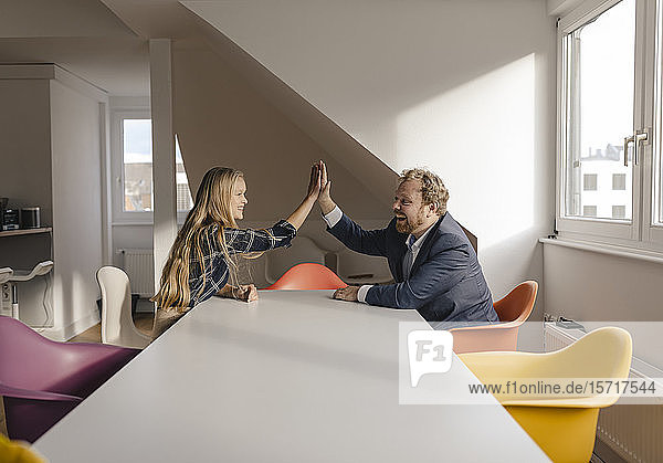 Businessman and businesswoman high fiving in office