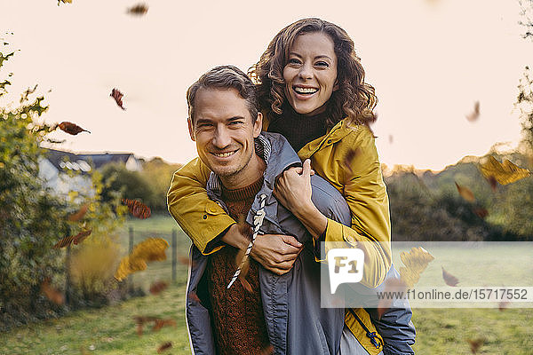 Portrait of man carrying woman piggyback outdoors in autumn