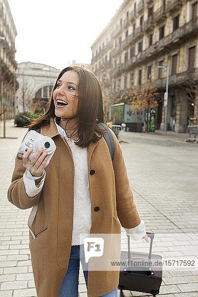 Glückliche junge Frau mit Koffer und Kamera in der Stadt unterwegs  Barcelona  Spanien