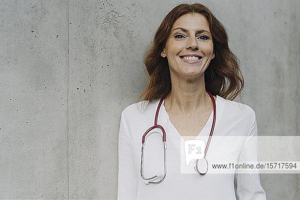 Porträt einer lächelnden Ärztin an einer Betonwand