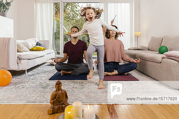 Exuberant girl with parents meditating at home