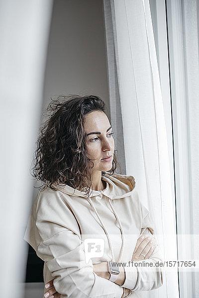 Porträt einer nachdenklichen Frau  die aus dem Fenster schaut