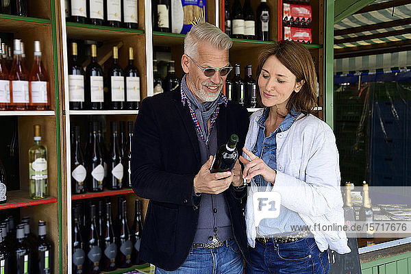Mature couple choosing bottle of wine at a wine shop