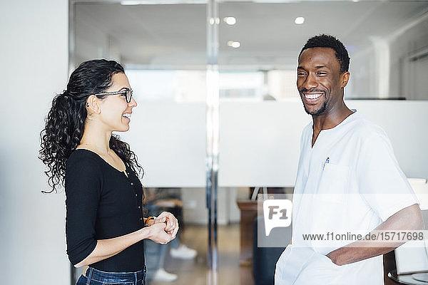 Lächelnder Zahnarzt mit Patient in der Zahnarztpraxis