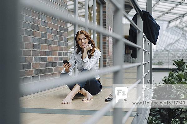 Geschäftsfrau  die in einem modernen Büro auf dem Boden sitzt