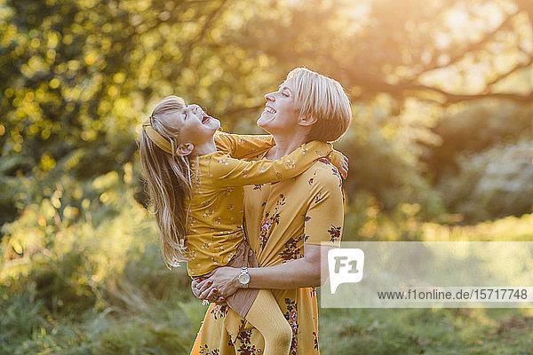 Mutter und kleine Tochter lachen gemeinsam in der Abenddämmerung