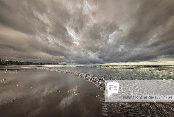 Neuseeland  Tongaporutu  Graue Wolken über sandigem Küstenstrand in der Abenddämmerung