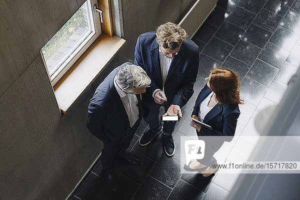 Geschäftsleute mit Smartphone sprechen in modernem Bürogebäude