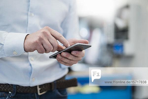 Nahaufnahme eines Geschäftsmannes mit einem Mobiltelefon in einer Fabrik