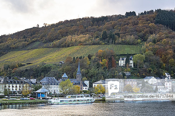 Germany  Rhineland-Palatinate  Traben-Trarbach  Ferries moored in front of houses of riverside town with hillside vineyard in background
