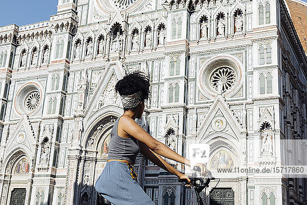 Young woman riding bicycle in front of cathedral  Florence  Italy